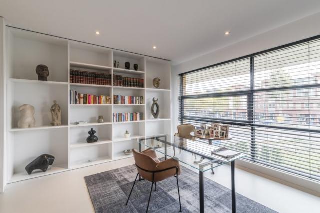 Bureau met boekenkast en beelden